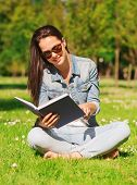 lifestyle, summer vacation, education, literature and people concept - smiling young girl reading bo