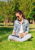lifestyle, summer vacation, education, drinks and people concept - smiling young girl writing to not