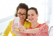 education, leisure and technology concept - two girlfriends taking selfie with smartphone camera
