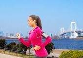 sport, fitness, health, technology and people concept - smiling young african american woman running