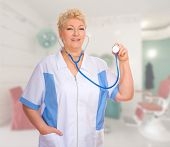 Mature doctor with stethoscope at medical office