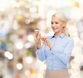 business, technology, holidays and people concept - smiling young businesswoman with smartphone