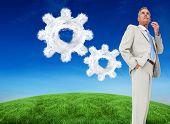 Thinking businessman against cloud cog and wheel
