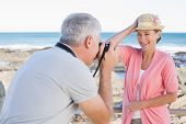 foto of take off clothes  - Happy casual man taking a photo of partner by the sea on a sunny day - JPG