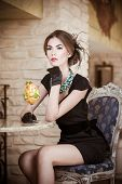 Fashionable attractive young woman in black dress sitting in restaurant. Beautiful brunette posing