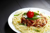 Spaghetti bolognese with fresh basil and tomato in white plate on back table