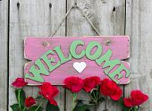 Pink weathered welcome sign with heart hanging on door with flower border of red roses