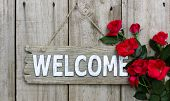 Wood welcome sign with red roses hanging on wooden door