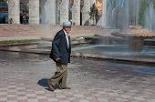 Elderly Asian Man Walking On Ala-too Square