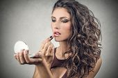 beautiful woman putting on her makeup