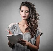 beautiful young woman who is writing