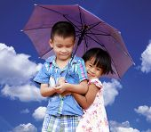 Smiling boy and little girl with umbrella