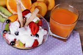 Fresh fruits salad with ice cream in bowl and juice on wooden background