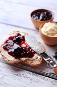 Fresh bread with homemade butter and blackcurrant jam on light wooden background