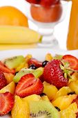 Fresh fruits salad in bowl with berries and juice close up