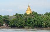 golden stupa on riverbank in Bagan