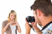 Man taking photo of his pretty girlfriend on white background