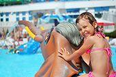 kleines Mädchen sitzen auf Spielzeug Elefant in der Nähe Pool in aquapark