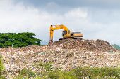 stock photo of landfills  - Crane on dumpsite use to clear garbage for landfill purpuses - JPG