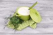 Green pan of cream with a tuft of dill and parsley in a basket on a napkin