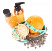 Fresh orange, tapeline, plate,bast, brush and sea stones scattered around on white background isolat