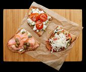 Three sandwiches on platter isolated over black