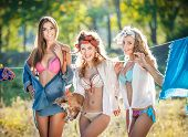 Three women with provocative outfits putting clothes to dry in sun. Sensual young females