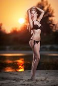 Portrait of young blonde girl in bikini posing provocatively at the beach in sunset