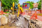 foto of crusher  - Yellow jackhammer is in construction site breaking old concrete - JPG