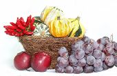 Wicker Basket With Gourd Pumpkins, Blue Grapes, Apples And Chili