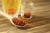 stock photo of saffron  - Spoon dry saffron on a background a glass with the infusion of saffron - JPG