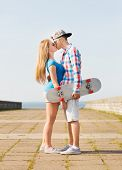 holidays, vacation, love and friendship concept - smiling couple with skateboard kissing outdoors
