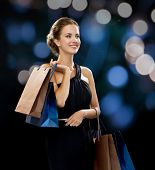 shopping, sale, gifts and holidays concept - smiling woman in dress with shopping bags over black ba
