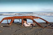 Man sits in rusting car wreck buried in sand
