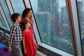 Mother with two children looking at evening city through a large window