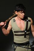 pic of mace  - Strong young man in a costume put mace on his shoulder in a dark studio - JPG