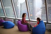 Woman talking with her daughter sitting on padded stools at the glass wall on a rainy day