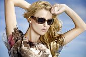 portrait of young adult beautiful sensuality blonde girl in sunglasses on background blue sky