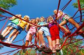 Children stand close on ropes of playground net