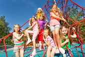 Smiling group of children sit on red ropes