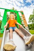 Boy sits on metallic chute and ready to slide