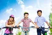 Three kids in helmets hold bike handle-bars