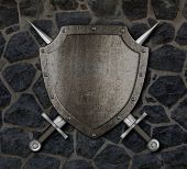 Medieval shield and crossed swords on stone wall