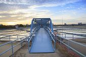 stock photo of big-rig  - perspective of metal bridge for working in big tank of water supply in metropolitan water works industry plant site - JPG