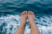 Woman's feet infron of the sea texture.