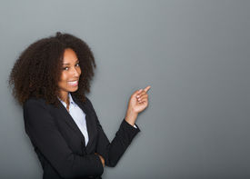 foto of finger  - Close up portrait of a friendly business woman pointing finger on gray background - JPG