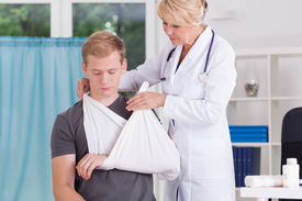 stock photo of fracture  - Doctor putting on sling to relive pain after fracture - JPG