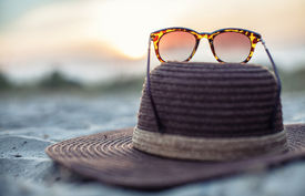 picture of headgear  - Hat and glasses lie on a beach at a beautiful sunset