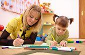 Teacher With Child In Preschool