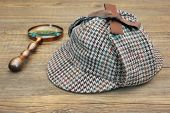 stock photo of sherlock  - Sherlock Holmes Hat or Deerstalker Hat and Retro Magnifying Glass on Wooden Table - JPG